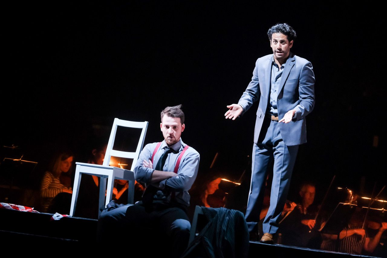 Richard sitting cross-armed on a stage with anger in his eyes
