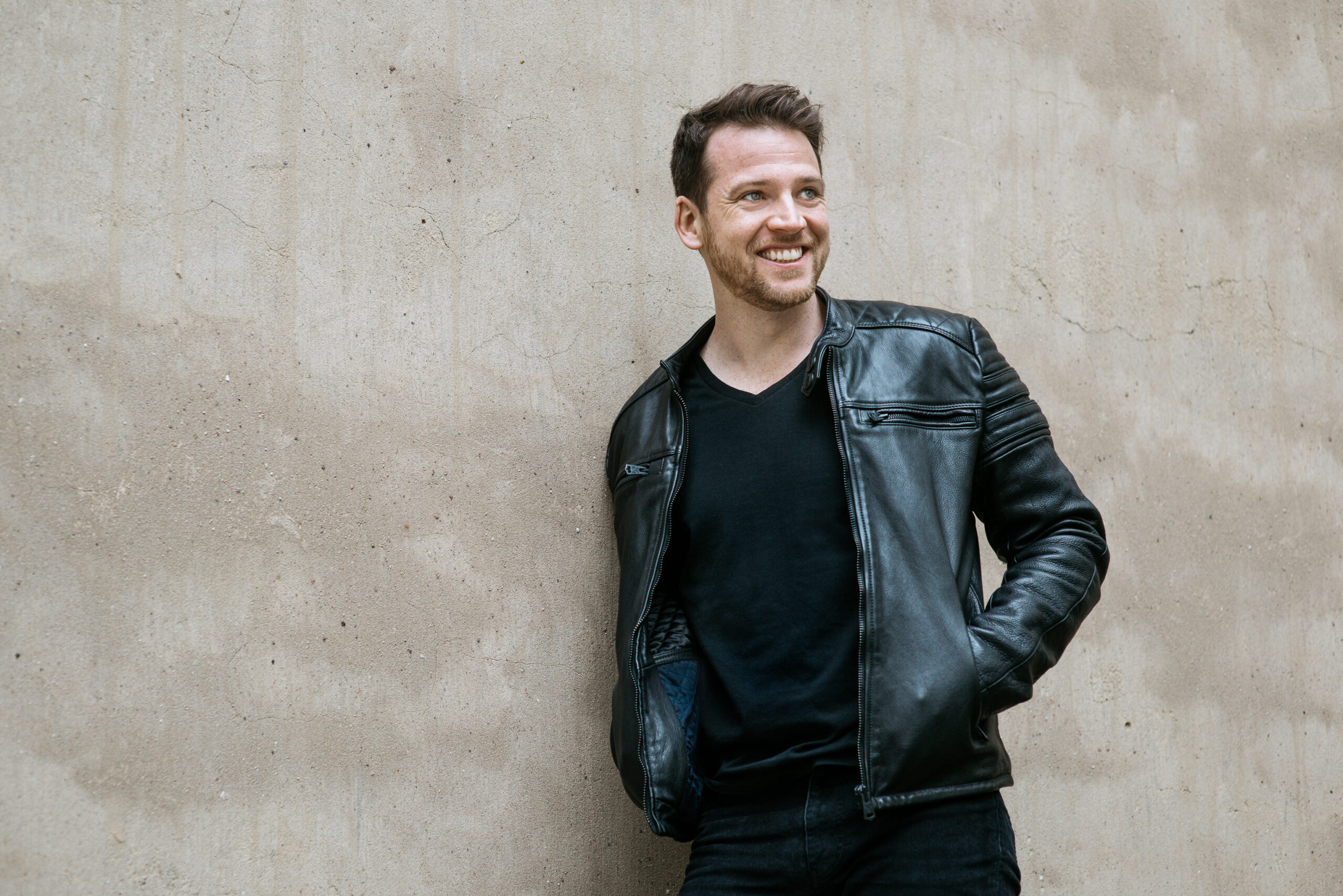 Richard leaning against a concrete wall, smiling.